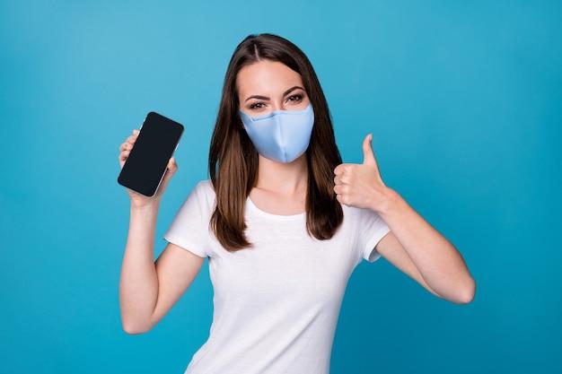 Portrait d'elle, elle a une fille aux cheveux bruns gaie et gaie recommandant un nouveau produit d'appareil montrant le pouce isolé sur fond de couleur bleu brillant et brillant porter un masque médical