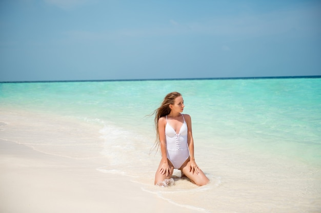 Portrait d'elle, elle, jolie fille aux cheveux longs, séduisante et mince, profitant d'une journée ensoleillée, beau temps, station balnéaire de luxe, station thermale, tourisme, assise sur du sable, eau claire et propre