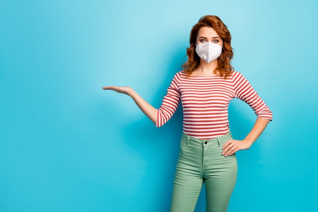 Portrait d'elle elle jolie fille foxy gingembre portant un masque de sécurité tenant un espace de copie sur la pollution de l'air de palme problème de co2 mers cov maladie isolée fond de couleur bleu vif vif