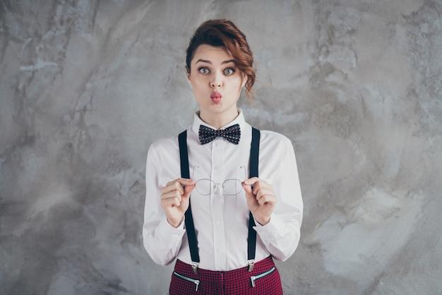 Portrait d'elle, elle, jolie, jolie, adorable, chic, mignonne, drôle, aux cheveux ondulés, mettant les spécifications hors de l'envoi d'un baiser d'air isolé sur fond de mur industriel en béton gris