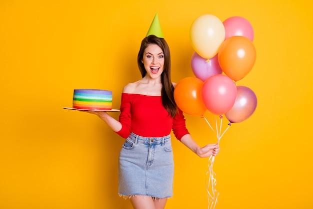 Portrait d'elle elle jolie jolie fille gaie assez gaie tenant dans la main des boules d'air de gâteau frais féliciter les salutations isolées brillantes vives éclat vibrant fond de couleur jaune