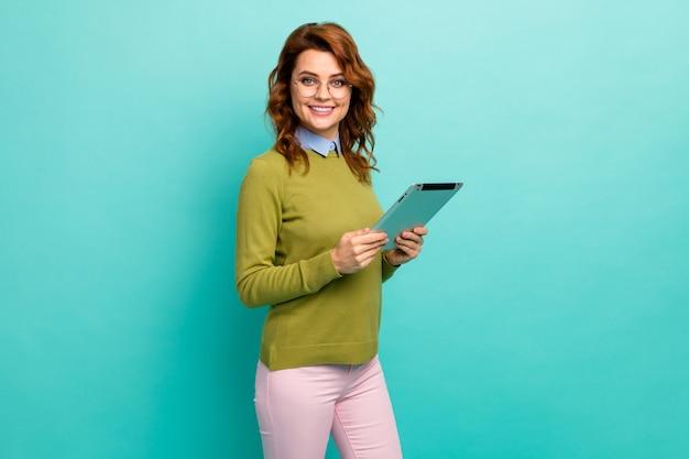 Portrait d'elle, elle jolie jolie fille joyeuse et joyeuse aux cheveux ondulés tenant dans les mains un didacticiel de cours sur le site web de navigation sur un ebook isolé sur un fond de couleur turquoise sarcelle éclatant et brillant