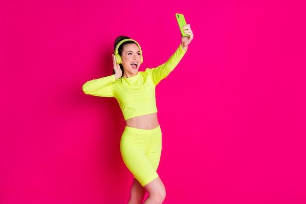 Portrait d'elle elle jolie jolie fille joyeuse et joyeuse écoutant de la musique s'amusant à faire du selfie passer du temps libre isolé brillant vif éclat rose vif fond de couleur fuchsia