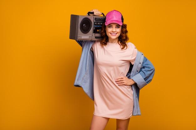 Portrait d'elle, elle, jolie, jolie, jolie, charmante, charmante, joyeuse, joyeuse, portant une boombox s'amusant isolée sur un fond de couleur jaune vif et brillant