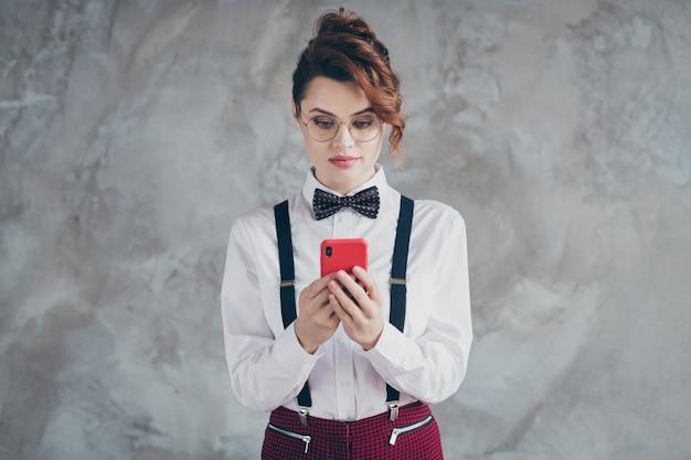Portrait d'elle, elle, jolie, jolie, jolie, chic, chic, sérieuse, focalisée, aux cheveux ondulés, utilisant une application cellulaire discutant isolée sur fond de mur industriel en béton gris