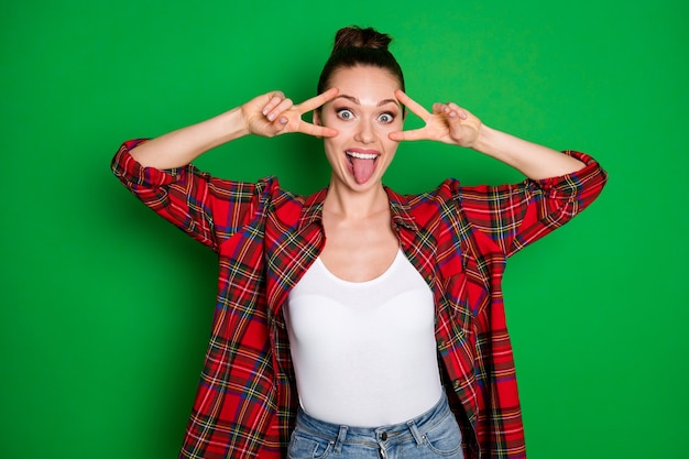 Portrait d'elle elle jolie jolie jolie fille folle gaie et gaie en chemise à carreaux montrant la langue du signe v trompant isolé sur fond de couleur vert vif éclatant brillant