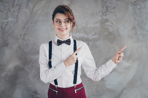Portrait d'elle elle jolie jolie jolie jolie fille aux cheveux ondulés gaie gaie et gaie pointant deux index annonce publicitaire isolée sur fond de mur industriel en béton gris