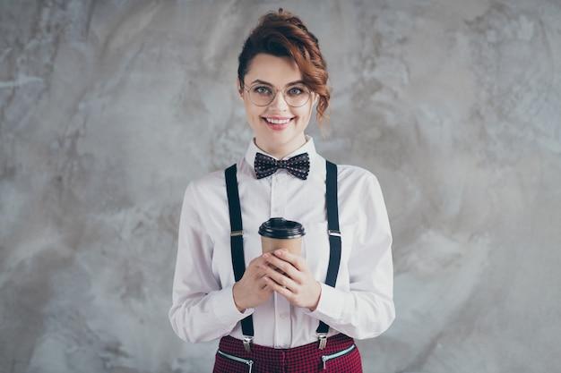 Portrait d'elle, elle, jolie, à la mode, séduisante, belle, classe, joyeuse, gaie, fille aux cheveux ondulés, buvant du latte isolé sur fond de mur industriel en béton gris