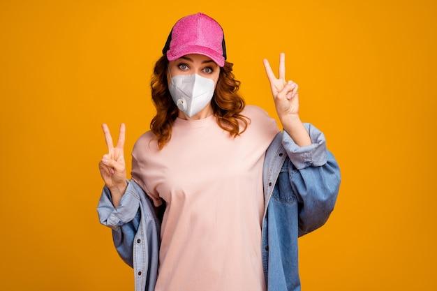 Portrait d'elle, elle séduisante fille aux cheveux ondulés en bonne santé portant un masque respiratoire de sécurité n95 montrant la prévention du double signe v mers cov isolé brillant vif éclat fond de couleur jaune vif
