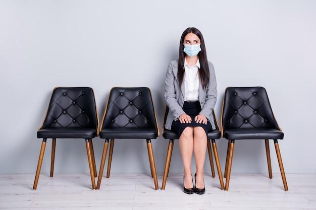 Portrait d'elle, elle séduisante gestionnaire de dame assise sur une chaise portant un masque de sécurité mers cov prévention de la grippe attente visite médecin clinique test diagnostic du syndrome isolé fond de couleur gris pastel