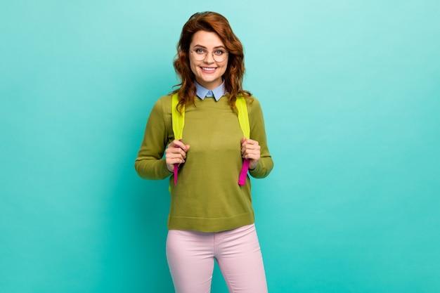 Portrait d'elle, jolie fille aux cheveux ondulés gaie, intelligente et gaie, retour à l'école, nouvel an le 1er septembre isolée sur fond de couleur turquoise sarcelle vibrant brillant éclatant