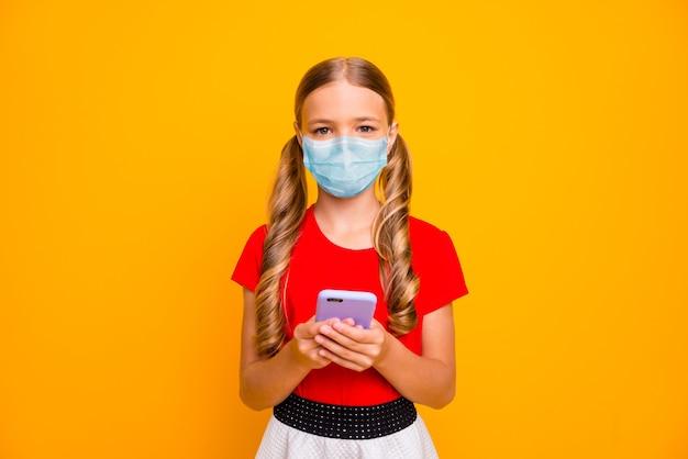 Portrait d'elle, jolie fille séduisante portant un masque de sécurité en gaze à l'aide d'un appareil numérique parcourir les actualités mers cov prévention pneumonie virale symptôme distance sociale isolé fond de couleur jaune vif