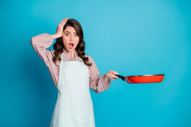 Portrait d'elle, jolie petite amie aux cheveux ondulés triste et inquiète, préparant la cuisson, friture, savoureux petit-déjeuner romantique isolé sur fond de couleur bleu vif et brillant
