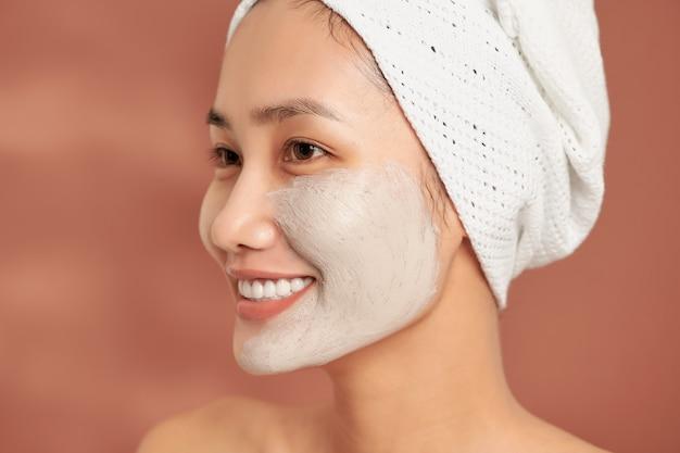 Portrait émotionnel d'une belle jeune femme nue heureuse et positive avec un masque cosmétique d'argile sur son visage