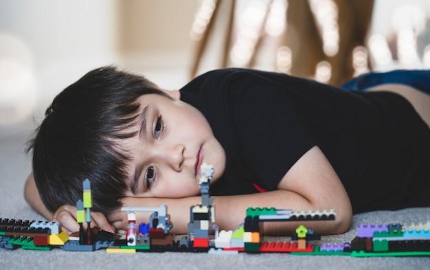 Portrait émotionnel enfant malheureux couché sur le plancher en bois avec son jouet de blocs en plastique.