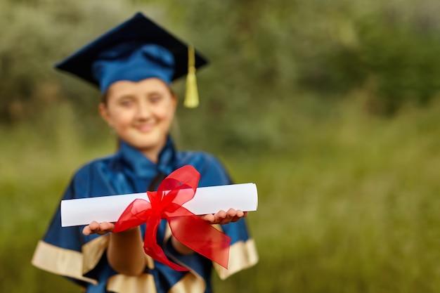 Portrait émotionnel d'une petite étudiante diplômée heureuse dans une robe de graduation bleue avec chapeau, titulaire d'un diplôme, en plein air. gros plan sur la main d'une diplômée mettant ses mains en l'air
