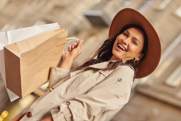 Portrait d'émotions positives d'une jeune femme excitée portant un manteau gris et un chapeau portant des achats