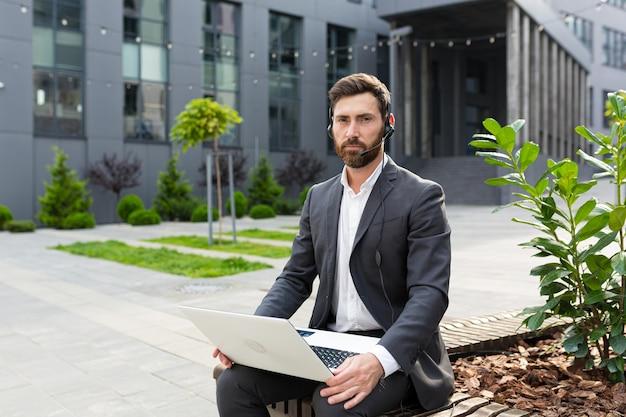 Portrait d'employé avec casque pour communication vidéo homme avec ordinateur portable sérieux regardant la caméra près du centre de bureau, travaillant et conseillant les clients à distance