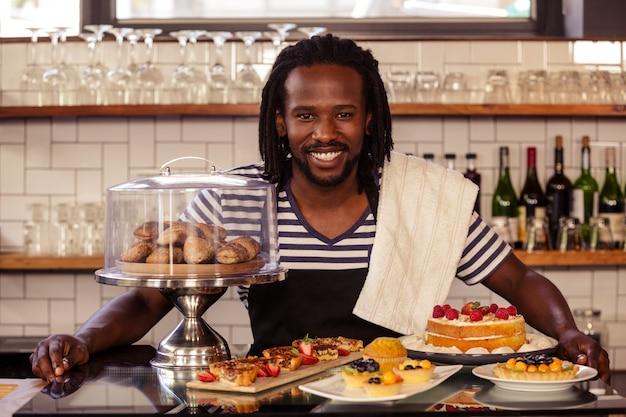 Portrait d'un employé hipster posant avec des pâtisseries