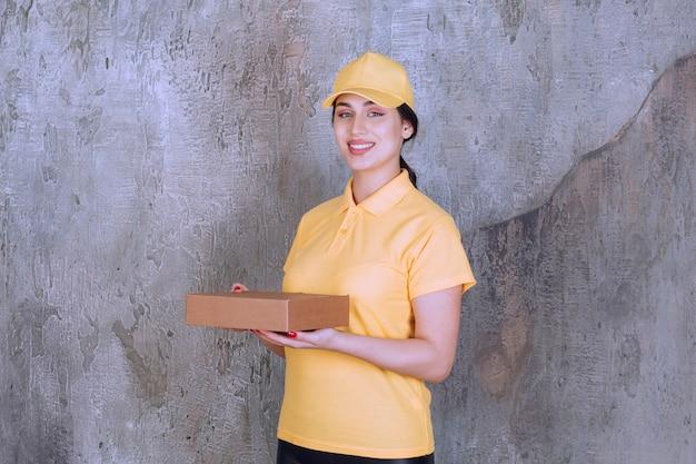 Portrait d'une employée de livraison tenant une boîte en carton