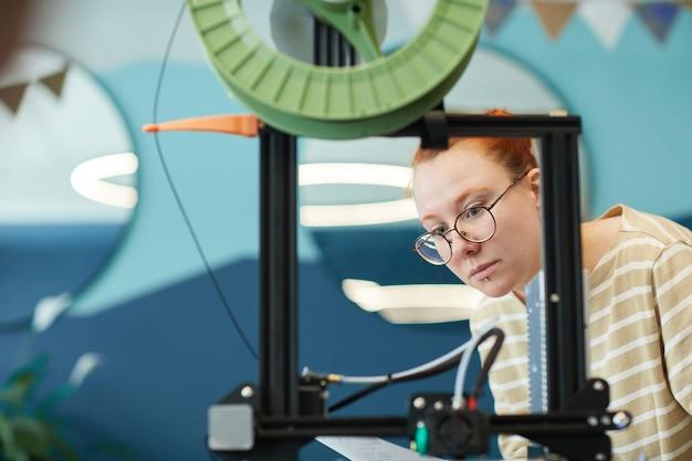 Portrait encadré d'une jeune femme aux cheveux rouges utilisant une imprimante 3d en classe d'ingénierie, espace de copie