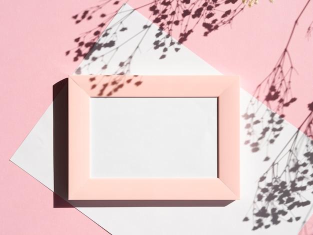 Portrait encadré de rose avec une couverture blanche sur un fond rose avec l'ombre des branches