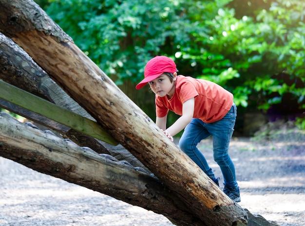 Portrait enfant actif grimper dans une cabane dans les arbres dans le parc forestier.