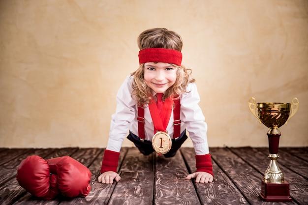 Portrait d'enfant d'affaires au bureau. succès, chef et enfant gagnant