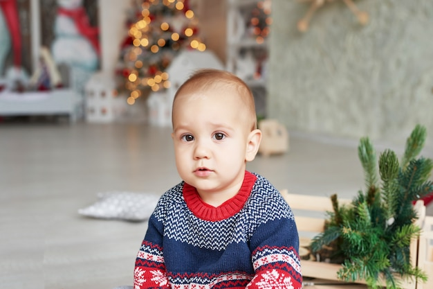 Portrait d'enfant bébé avec l'arbre de noël. tout-petit mignon de noël. concept de vacances en famille. salle de jeux pour enfants. noël dans la chambre des enfants.
