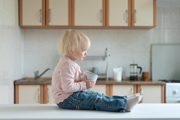 Portrait d'enfant blond dans la cuisine avec une tasse dans ses mains. vue de côté.