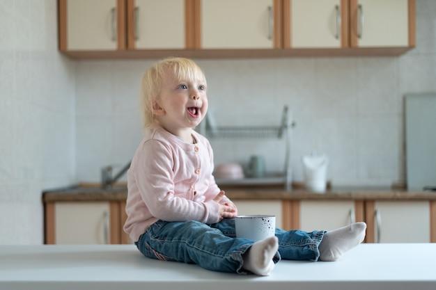Portrait d'enfant blonde drôle avec tasse sur cuisine