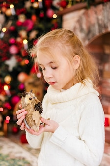 Portrait d'enfant blonde heureuse fille en pull blanc tenant jouet hibou