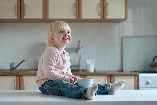 Portrait d'enfant blonde souriante avec tasse sur table de cuisine. petit déjeuner en famille.