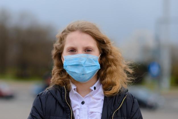 Portrait d'enfant caucasien triste en masque facial sur une aire de jeux fermée en plein air. quarantaine à distance sociale du coronavirus.