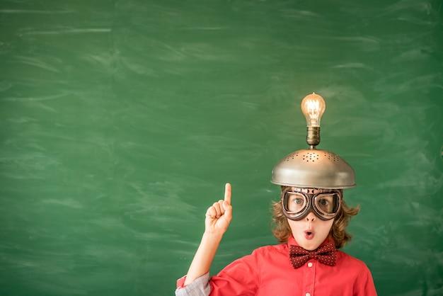 Portrait d'enfant en classe enfant avec casque de réalité virtuelle jouet en classe retour à l'école