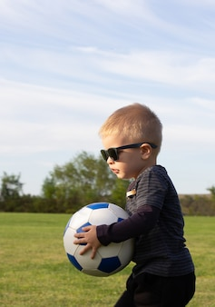 Portrait d'enfant cool tout-petit dans des lunettes de soleil debout dans un terrain en herbe, une jambe sur un ballon de football. petit joueur de football élégant au terrain de jeu ou au parc. concept actif d'enfance et de sport pour les enfants