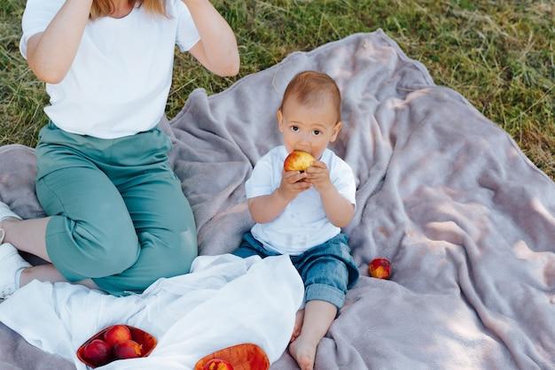 Portrait d'enfant drôle regardant la caméra et mangeant des fruits, pique-nique familial en plein air. maman et son petit fils sont assis sur une couverture sur l'herbe verte, se reposant sur l'heure d'été de la nature. image recadrée