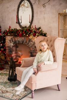 Portrait d'enfant fille blonde heureuse en chandail blanc, implantation dans le fauteuil rose