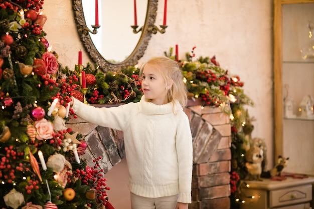Portrait d'enfant fille blonde heureuse en pull blanc, implantation sur le sol