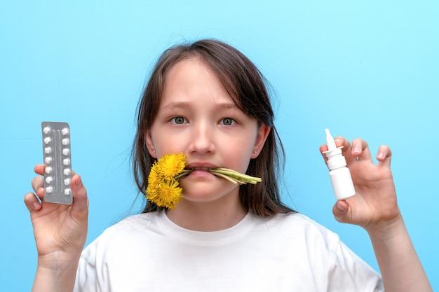 Portrait d'une enfant fille avec des fleurs dans ses dents et des pilules anti-allergiques et un spray dans ses mains