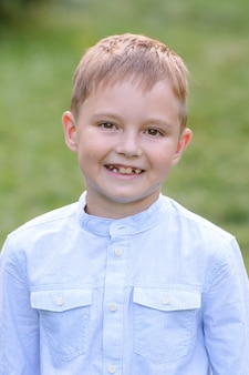 Portrait d'un enfant garçon à l'extérieur sur une chaude journée d'été ensoleillée. le garçon sourit. le garçon a perdu des dents de lait.