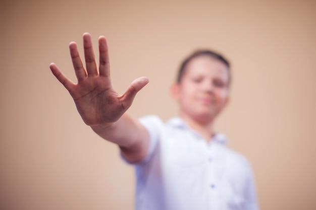 Portrait d'enfant garçon montrant le geste d'arrêt. concept d'enfants et d'émotions