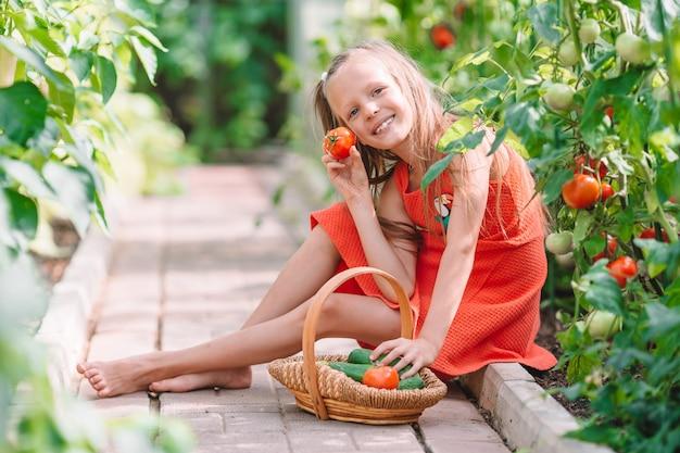 Portrait d'enfant avec la grosse tomate dans les mains en serre