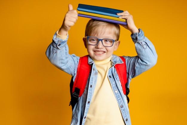 Portrait d'un enfant heureux 5-6 ans sur un mur jaune avec des livres et un sac à dos, l'éducation des enfants.