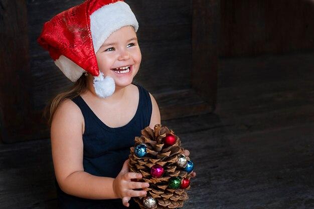 Portrait d'un enfant heureux avec cône de sapin pune