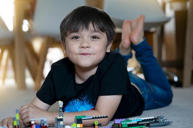 Portrait enfant jouant des blocs en plastique, happy child boy allongé sur de la moquette la construction de ses jouets colorés