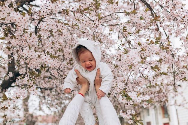 Portrait d'enfant joyeux joyeux en vêtements blancs sur fond de fleur arbre fleurs.