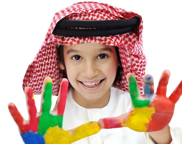 Portrait d'enfant musulman arabe avec de la couleur sur ses mains