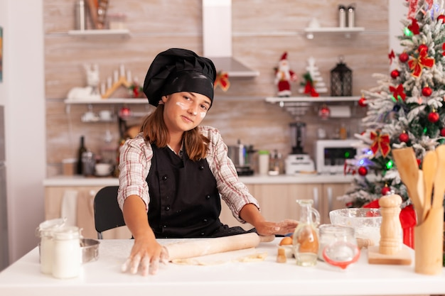 Portrait d'enfant portant un tablier préparant de la pâte maison à l'aide d'un rouleau à pâtisserie