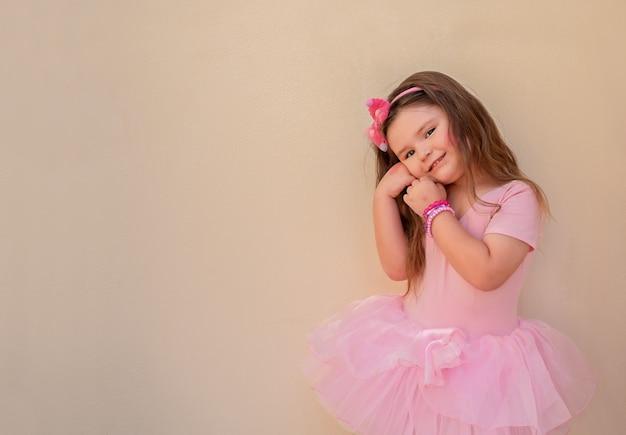 Portrait d'un enfant en robe de ballet. fille posant, mignonne a plié ses mains près de son visage et souriant